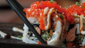 Η κινηματογράφηση σε πρώτο πλάνο chopsticks κρατά ότι τα σούσια κυλούν ένα πιάτο στο εστιατόριο ιαπωνικός παραδοσιακός κουζίνας απόθεμα βίντεο