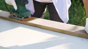 Η κινηματογράφηση σε πρώτο πλάνο woodworker παραδίδει τα προστατευτικά γυαλιά που στρώνουν με άμμο την ξύλινη σανίδα απόθεμα βίντεο