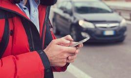 Η κινηματογράφηση σε πρώτο πλάνο ενός ατόμου δίνει την κλήση ενός ταξί με ένα smartphone app Στοκ Εικόνες