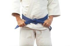 Η κινηματογράφηση σε πρώτο πλάνο ενός ατόμου σε ένα άσπρο κιμονό για το τζούντο, δεσμοί επάνω ένα μπλε είναι Στοκ Φωτογραφίες