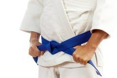 Η κινηματογράφηση σε πρώτο πλάνο ενός ατόμου σε ένα άσπρο κιμονό για το τζούντο, δεσμοί επάνω ένα μπλε είναι Στοκ εικόνα με δικαίωμα ελεύθερης χρήσης