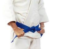 Η κινηματογράφηση σε πρώτο πλάνο ενός ατόμου σε ένα άσπρο κιμονό για το τζούντο, δεσμοί επάνω ένα μπλε είναι Στοκ Εικόνες