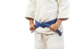 Η κινηματογράφηση σε πρώτο πλάνο ενός ατόμου σε ένα άσπρο κιμονό για το τζούντο, δεσμοί επάνω ένα μπλε είναι Στοκ φωτογραφία με δικαίωμα ελεύθερης χρήσης