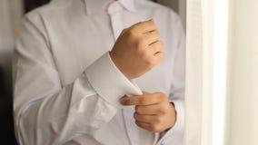 Η κινηματογράφηση σε πρώτο πλάνο ενός ατόμου χεριών πώς φορά το πουκάμισο και το μανικετόκουμπο, άτομο έντυσε στο γάμο απόθεμα βίντεο