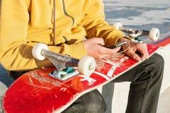 Η κινηματογράφηση σε πρώτο πλάνο ενός εφήβου έντυσε στα τζιν και τα πάνινα παπούτσια μπλουζών καθμένος σε ένα πάρκο σαλαχιών κρατ Στοκ Εικόνες