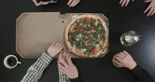Η κινηματογράφηση σε πρώτο πλάνο επάνω από την άποψη των χεριών που βάζουν την πίτσα στον πίνακα Το άτομο παίρνει τη φωτογραφία τ φιλμ μικρού μήκους