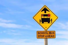 Η κινηματογράφηση σε πρώτο πλάνο μιας στάσης σχολικών λεωφορείων υπογράφει μπροστά ενάντια σε έναν μπλε ουρανό Στοκ Φωτογραφίες