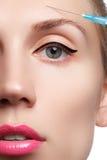 Η κινηματογράφηση σε πρώτο πλάνο της όμορφης γυναίκας παίρνει την έγχυση Όμορφο πρόσωπο και η σύριγγα (πλαστική χειρουργική και κ Στοκ εικόνα με δικαίωμα ελεύθερης χρήσης