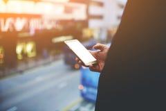 Η κινηματογράφηση σε πρώτο πλάνο του αρσενικού με το τηλέφωνο κυττάρων υπό εξέταση με το κενό υπόβαθρο επίδειξης για διαφημίζει τ Στοκ Φωτογραφίες