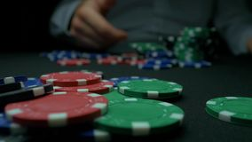 Η κινηματογράφηση σε πρώτο πλάνο του ατόμου που ρίχνει ένα πόκερ πελεκά σε σε αργή κίνηση Κινηματογράφηση σε πρώτο πλάνο του χερι φιλμ μικρού μήκους