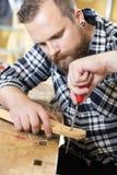 Η κινηματογράφηση σε πρώτο πλάνο του βιοτέχνη αρχειοθετεί τον ξύλινο λαιμό κιθάρων στο εργαστήριο στοκ φωτογραφία με δικαίωμα ελεύθερης χρήσης