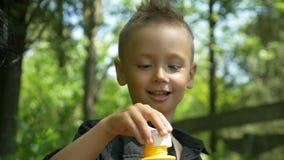 Η κινηματογράφηση σε πρώτο πλάνο του ευτυχούς χαριτωμένου αγοριού που φυσά το χρωματισμένο σαπούνι βράζει σε ένα ηλιόλουστο πάρκο φιλμ μικρού μήκους