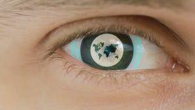 Η κινηματογράφηση σε πρώτο πλάνο του ματιού με το κείμενο υπολογιστών Ζουμ στο centr πλανήτης Γη σημαδιών απεικόνιση αποθεμάτων