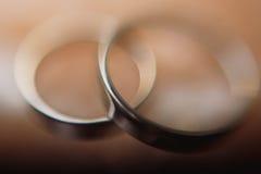 Η κινηματογράφηση σε πρώτο πλάνο των ασημένιων γαμήλιων δαχτυλιδιών ζευγών, πολυτέλεια δύο χρυσή δεσμεύει Στοκ Φωτογραφίες