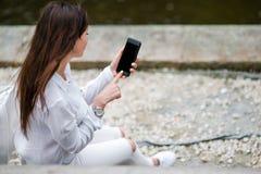 Η κινηματογράφηση σε πρώτο πλάνο των θηλυκών χεριών κρατά το κινητό τηλέφωνο υπαίθρια στην οδό Άτομο που χρησιμοποιεί το κινητό s Στοκ Εικόνα