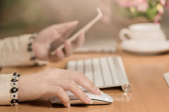 Η κινηματογράφηση σε πρώτο πλάνο των σύγχρονων χεριών επιχειρησιακών γυναικών χτυπά το έξυπνο τηλέφωνο ποντικιών και χρήσης Στοκ Φωτογραφία