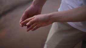 Η κινηματογράφηση σε πρώτο πλάνο των χεριών ενός νέου ζεύγους κτυπά ελαφρά ήπια η μια την άλλη στην παραλία φιλμ μικρού μήκους