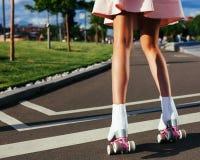 Η κινηματογράφηση σε πρώτο πλάνο των όμορφων θηλυκών ποδιών στον κύλινδρο κάνει πατινάζ σε μια απότομη θερινή εξάρτηση στο δρόμο Στοκ εικόνα με δικαίωμα ελεύθερης χρήσης