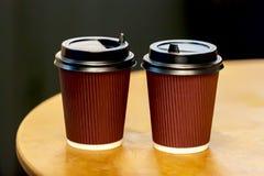 Η κινηματογράφηση σε πρώτο πλάνο δύο καφετιά μίας χρήσης φλυτζάνια με το φρέσκο espresso χύνει Πολιτισμός καφέ, επαγγελματικός κα Στοκ φωτογραφία με δικαίωμα ελεύθερης χρήσης