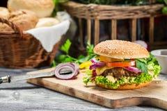 Κινηματογράφηση σε πρώτο πλάνο burger που γίνονται ââfrom beaf και των φρέσκων λαχανικών Στοκ Φωτογραφία