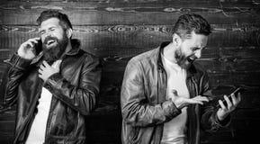 Η κινητή συνομιλία και συνδέει Επιχειρησιακή κλήση Βάναυσο γενειοφόρο hipster ατόμων σε μοντέρνη χρήση σακακιών δέρματος κινητή στοκ εικόνες