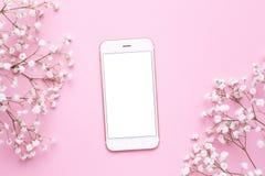 Η κινητή τηλεφωνική χλεύη επάνω και τα άσπρα λουλούδια στη ρόδινη άποψη επιτραπέζιων κορυφών κρητιδογραφιών στο επίπεδο βάζουν το στοκ φωτογραφία με δικαίωμα ελεύθερης χρήσης
