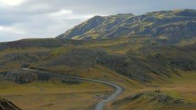 Η κοιλάδα του ηφαιστειακού καλυμμένου βουνά κιτρινισμένου βρύου, δρόμος το διασχίζει και το μικρό αυτοκίνητο κινείται φιλμ μικρού μήκους