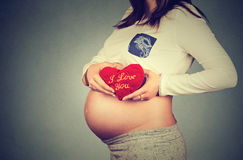 Η κοιλιά της εγκύου γυναίκας με την καρδιά διαμόρφωσε το κόκκινο μαξιλάρι Ανθρώπινη έννοια εγκυμοσύνης Στοκ Εικόνες