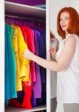 Η κοκκινομάλλης γυναίκα επιλέγει τα ενδύματά της κοντά στο ντουλάπι θρόμβος στοκ φωτογραφίες με δικαίωμα ελεύθερης χρήσης