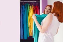 Η κοκκινομάλλης γυναίκα επιλέγει τα ενδύματά της κοντά στο ντουλάπι θρόμβος στοκ εικόνα με δικαίωμα ελεύθερης χρήσης