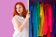 Η κοκκινομάλλης γυναίκα επιλέγει τα ενδύματά της κοντά στο ντουλάπι θρόμβος στοκ εικόνες