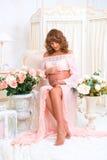 Η κοκκινομάλλης έγκυος γυναίκα κάθεται στην καρέκλα και εξετάζει την κοιλιά με την αγάπη στοκ φωτογραφίες με δικαίωμα ελεύθερης χρήσης