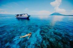 Η κολύμβηση με αναπνευστήρα στην μπλε θάλασσα κοντά σε Krakatau τοποθετεί στοκ εικόνες