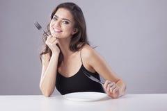 Η κομψή γυναίκα κάθεται με το μαχαίρι και το δίκρανο Στοκ Φωτογραφία