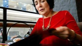 Η κομψή ηλικίας γυναίκα στο κόκκινο φόρεμα, καυκάσιο έθνος, διαβάζει τις επιλογές απόθεμα βίντεο