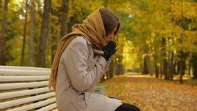 Η κομψή νέα γυναίκα αισθάνεται κρύα καθμένος σε έναν πάγκο στο πάρκο φθινοπώρου απόθεμα βίντεο