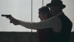 Η κομψή νέα γυναίκα πορτρέτου στο κόκκινο φόρεμα που στοχεύει ένα πυροβόλο όπλο, όμορφος γενναίος άνδρας στέκεται πίσω, κατευθύνο απόθεμα βίντεο