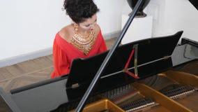 Η κομψή νέα γυναίκα στο κομψό κόσμημα παίζει το pianoforte σε σε αργή κίνηση απόθεμα βίντεο