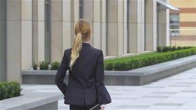 Η κομψή ξανθή επιχειρησιακή γυναίκα με τον υπολογιστή ταμπλετών πηγαίνει γύρω από το κτίριο γραφείων κίνηση αργή φιλμ μικρού μήκους