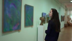 Η κομψή όμορφη γυναίκα εξετάζει τις εικόνες στο μουσείο της σύγχρονης τέχνης Έργα ζωγραφικής έργου της τέχνης στην έκθεση φιλμ μικρού μήκους