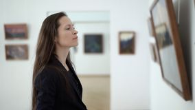 Η κομψή όμορφη γυναίκα κινηματογραφήσεων σε πρώτο πλάνο εξετάζει τις εικόνες στο μουσείο της σύγχρονης τέχνης Φωτογραφίες προσοχή απόθεμα βίντεο