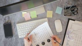 Η κορυφή της γυναίκας υπάλληλος άποψης κρατά το έγγραφο, γραφική παράσταση και παίρνει τις σημειώσεις με το μολύβι, κάθισμα στην  απόθεμα βίντεο