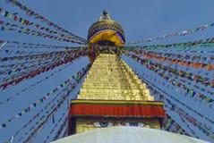 Η κορυφή του βουδιστικού stupa Bodnath: ο χρυσός θόλος και τα μάτια του Βούδα κάτω από το, οι θιβετιανές σημαίες προσευχής σε δια Στοκ Φωτογραφία