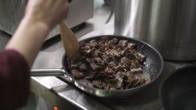 Η κουζίνα ψήνει το κρέας στο τηγάνι στη βιομηχανική κουζίνα στο εστιατόριο απόθεμα βίντεο