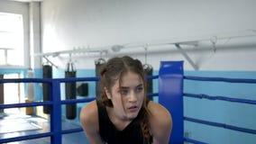 Η κουρασμένη γυναίκα αθλητών αναπνέει βαθειά και στηρίζεται μετά από σκληρά να εκπαιδεύσει στην αθλητική λέσχη στην κινηματογράφη απόθεμα βίντεο