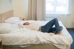 Η κουρασμένη γυναίκα βρίσκεται στο κρεβάτι με το βραχίονά της στο κεφάλι και τα μάτια Η νέα γυναίκα με μακρυμάλλη, φορά τα τζιν Στοκ Φωτογραφίες