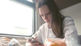 Η κουρασμένη γυναίκα διαβάζει ένα βιβλίο στο smartphone που ταξιδεύει σε ένα μεγάλης απόστασης τραίνο φιλμ μικρού μήκους