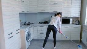 Η κουρασμένη γυναίκα πλένει το πάτωμα κουζινών με μια σφουγγαρίστρα απόθεμα βίντεο