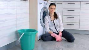 Η κουρασμένη γυναίκα στα ρόδινα λαστιχένια γάντια στο πάτωμα κουζινών μετά από να καθαρίσει εξετάζει τη κάμερα φιλμ μικρού μήκους