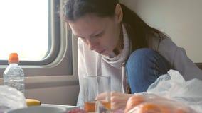 Η κουρασμένη γυναίκα τρώει και διαβάζει τις ειδήσεις στο τηλέφωνο που ταξιδεύει με το τραίνο στη δεύτερης θέσης μεταφορά απόθεμα βίντεο